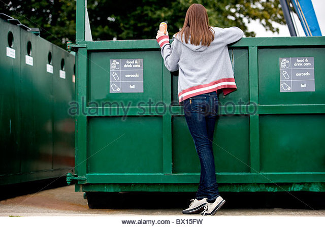 A teenage girl recycling a drink can, rear view - Stock Image