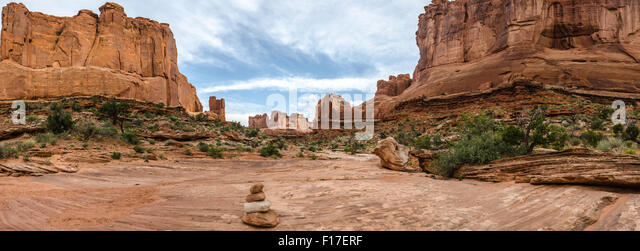 Rock cairns mark hikers' way through the rock formations known as Park Avenue in Arches National Park - Stock Image
