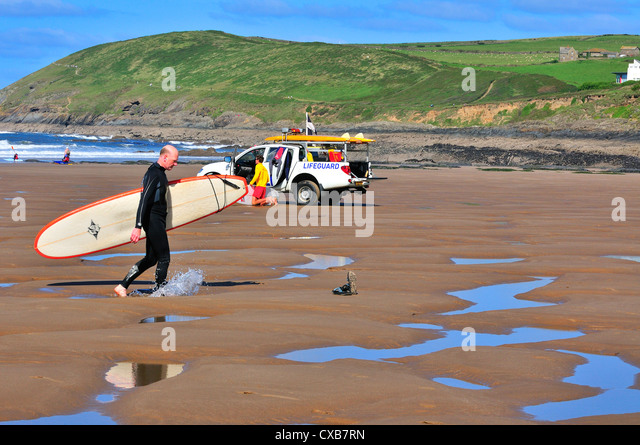 Mature surfer walks across Croyde Beach, after surfing . Croyde, North Devon, United Kingdom.with RNLI life guard - Stock Image