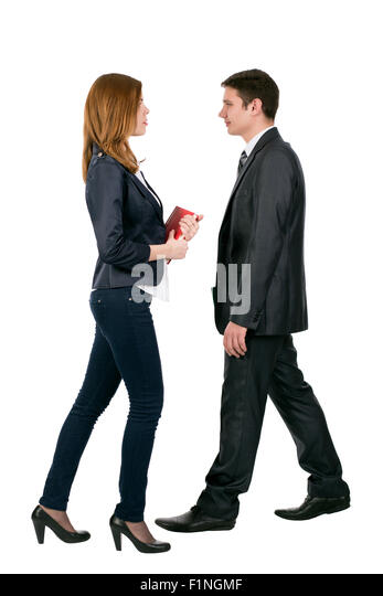 Officially dressed male and female walking towards each other - Stock Image