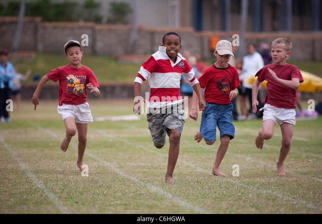 Primary school children running in inter-house athletics race - Stock Image