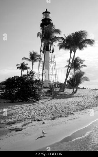 In this black and white image of the Hillsboro Lighthouse early morning sun from the east casts long shadows of - Stock Image