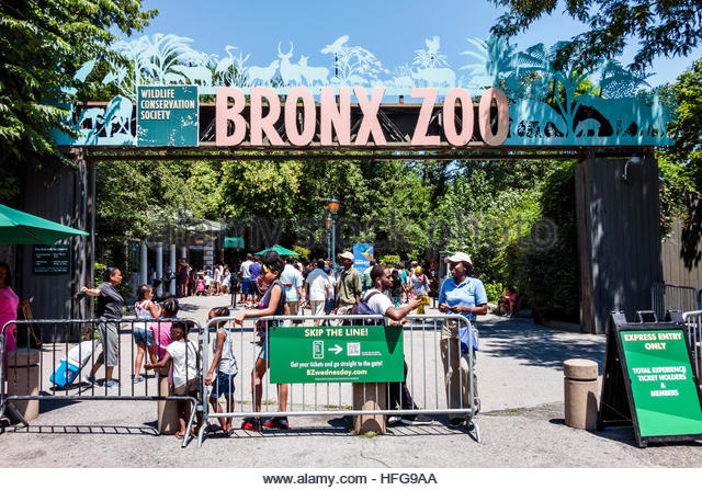 New York New York City NYC Bronx Bronx Zoo entrance ticket taker gate Black man woman family child sign - Stock Image