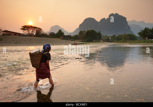 a woman fording the Nam Song River at Vang Vieng, Laos - Stock-Bilder