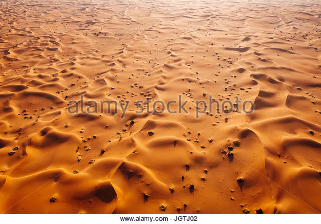 Aerial landscape photo of sand dunes of the Arabian desert during sunrise. - Stock Image