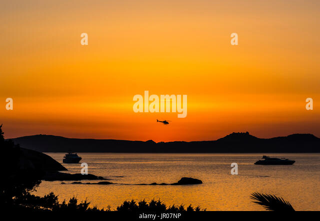 Helicopter flying in a fabulous orange sunset over Sardinia, Italy - Stock Image