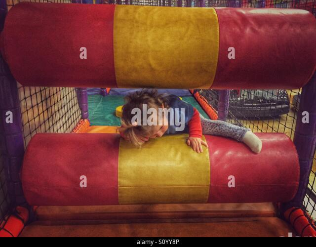 Toddler playing in inside playground - Stock Image