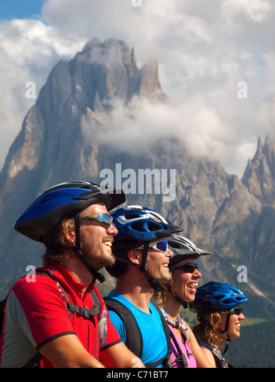 Four happy mountain bikers are gazing at the rock cliffs of Seiser Alm. - Stock Image