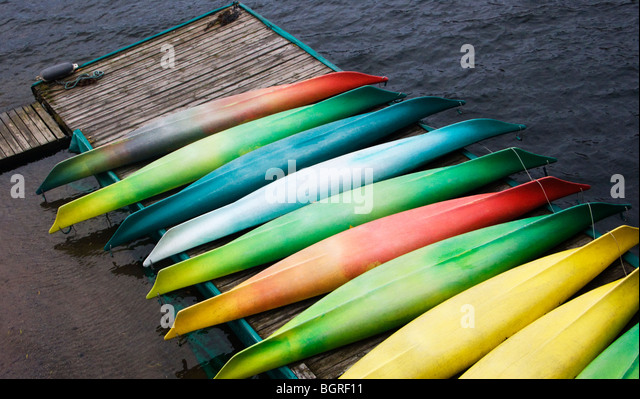 Kayaks in different colors on a jetty, Sweden. - Stock Image