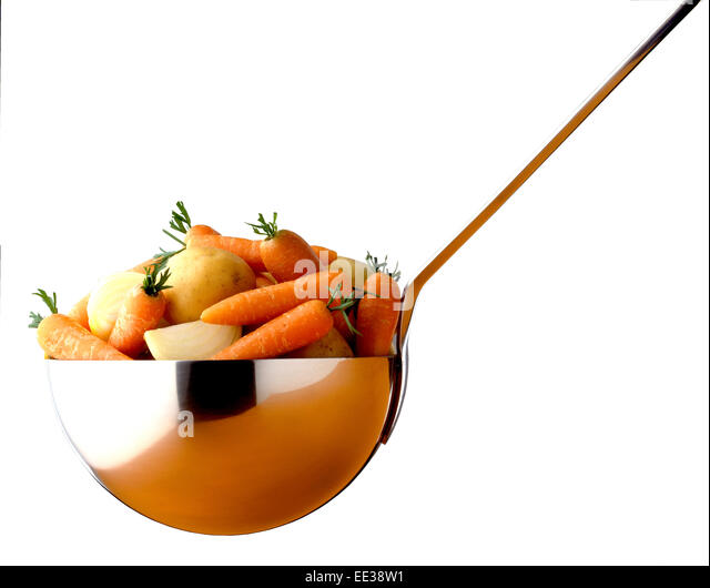 carrot soup ingredients in large ladle - Stock Image