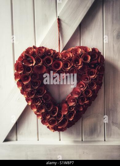 Heart of flowers. Red love heart shape formed of flowers. Love and romance or Valentines symbol. - Stock Image