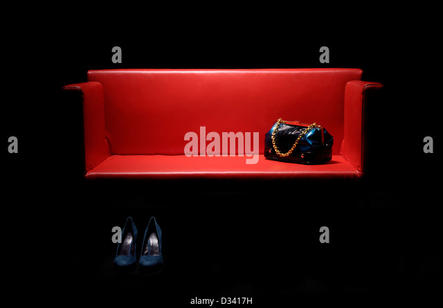 red leather couch with handbag and women's footwear. - Stock Image