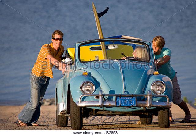 Young men pushing convertible car by sea - Stock Image