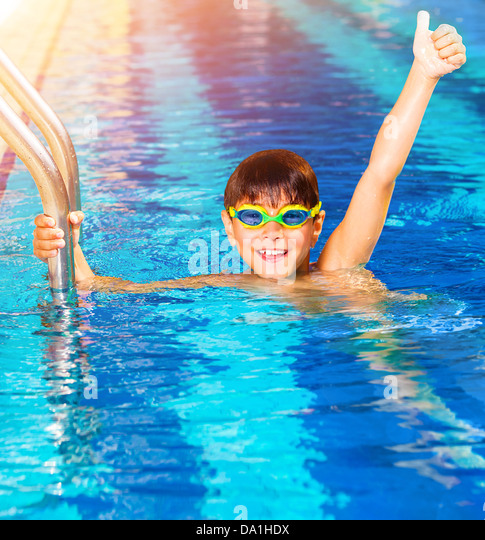 Closeup on little boy wearing swimming goggles in the pool, junior swimming competition, happy winner with raised - Stock Image