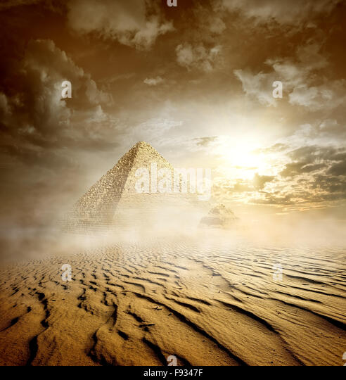Storm clouds and pyramids in sand desert - Stock Image