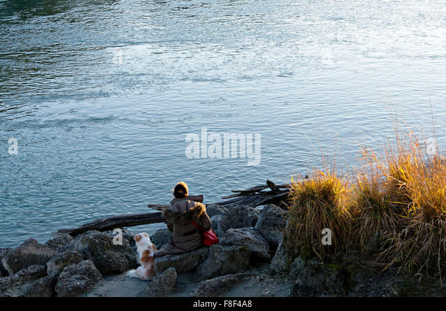 Woman with dog sitting on River Inn foreshore, Wasserburg, Upper Bavaria, Germany, Europe. - Stock Image