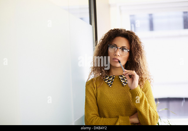 Female office worker holding pen - Stock-Bilder
