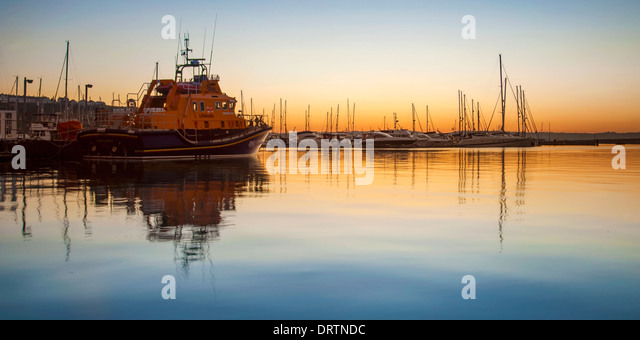 Torbay lifeboat moored in Brixham marina at sunset. - Stock Image