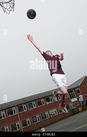 A teenage schoolboy boy playing basketball at a secondary school UK - Stock Image