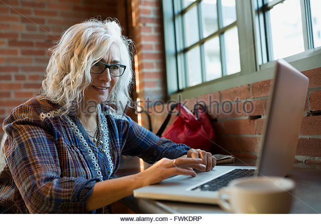 Woman working on laptop in coffee shop - Stock Image