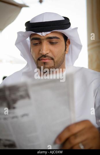 Arab Business Man Reading Newspaper on Patio - Stock Image