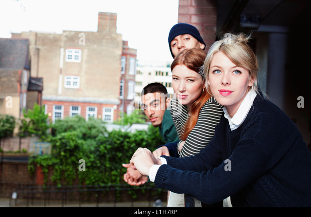 Four young adults, standing on balcony in London, UK - Stock Image