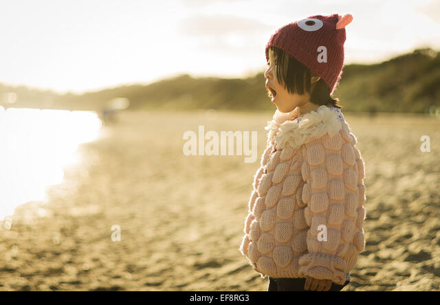 Australia, Melbourne, Young girl singing on sandy beach - Stock Image