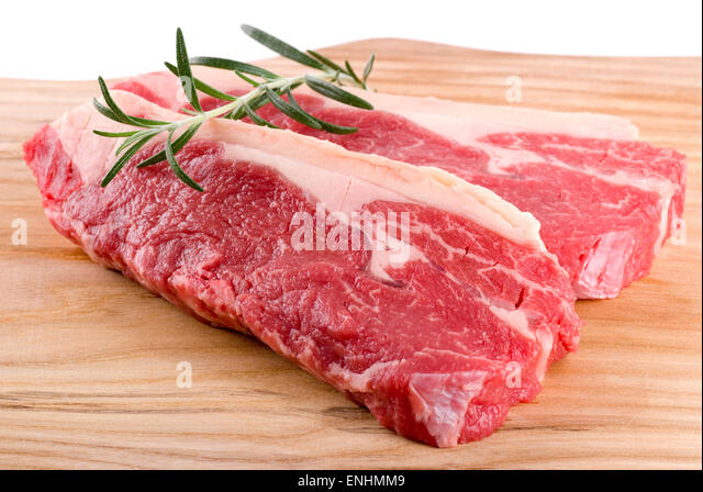 Two fresh steaks with a rosemary branch. - Stock Image