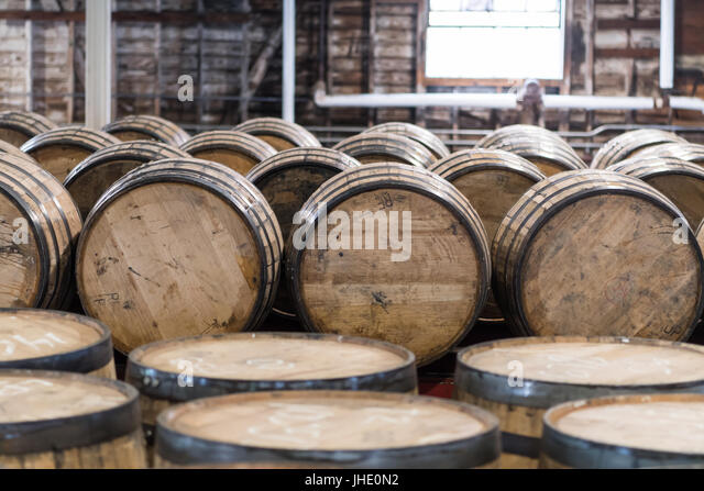 Bourbon Barrel Storage Room with barrels standing and rolling - Stock Image