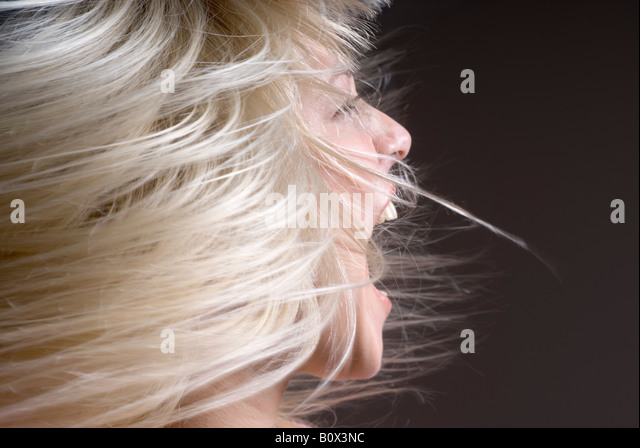 A woman tossing her hair with her mouth open - Stock Image