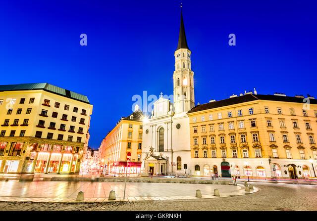 Vienna, Austria. Michaelerplatz, wide-angle view at dusk with Michaelkirche, Habsburg Empire landmark in Wien - Stock Image