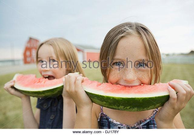 Portrait of girls eating watermelon slices outdoors - Stock-Bilder