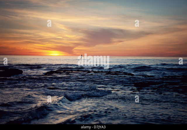 Paddle boarder in the ocean, far away in the distance at sunset - Stock Image
