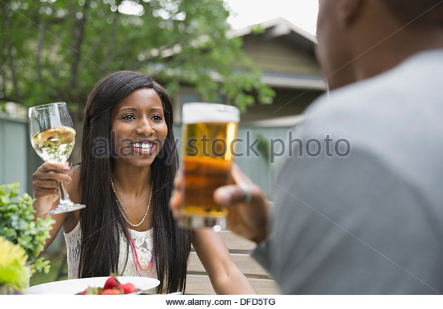 Cheerful couple enjoying a drink in backyard - Stock Image
