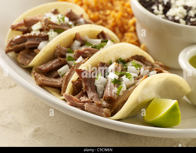Three carnitas street tacos topped with onion and cilantro served with black beans and Spanish rice - Stock Image