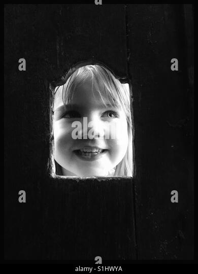 Girls face through a hole in a wooden door. - Stock Image