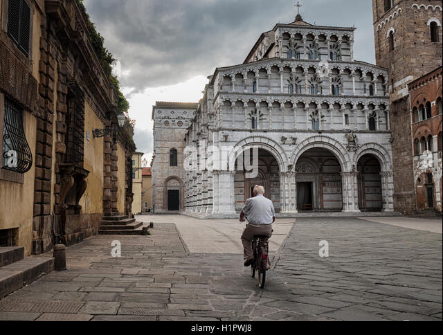 A cyclist rides to work in the morning across the cathedral square at Lucca, Tuscany, Italy - Stock Image