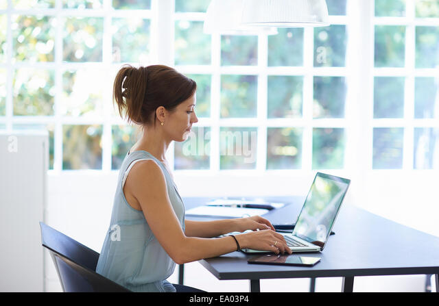 Mid adult woman working on laptop in dining room - Stock Image