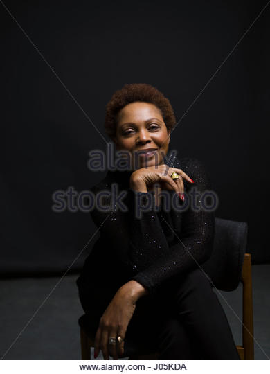 Portrait confident African American woman sitting on chair against black background - Stock Image