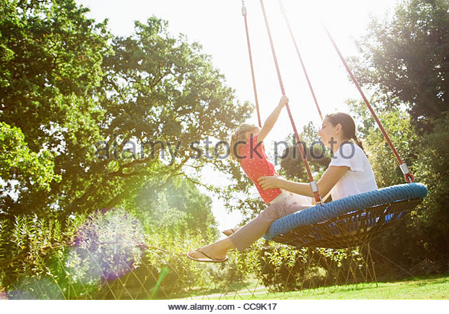 Mother and daughter on swing in sunny park - Stock-Bilder