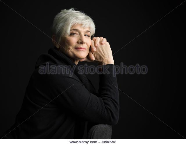 Portrait confident senior woman with short white hair against black background - Stock Image