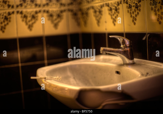 Syringe on broken sink - Stock Image