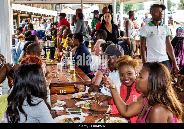 Johannesburg South Africa African Soweto Vilakazi Street Precinct Sakhumzi restaurant Black woman man friends eating - Stock Image