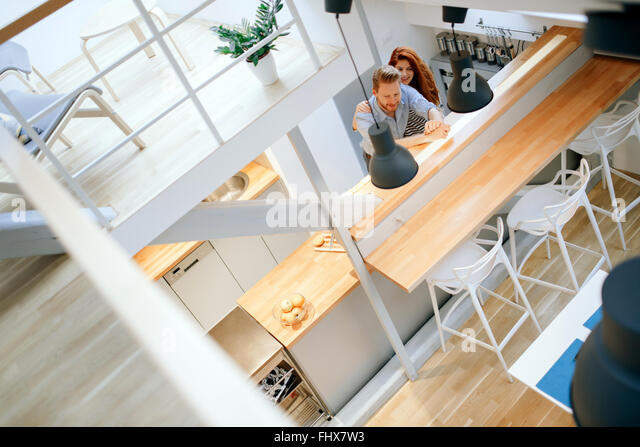 Beautiful couple posing in well designed kitchen - Stock Image
