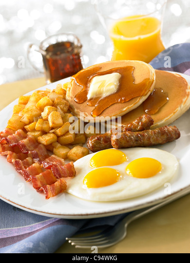 Pancake breakfast with eggs, bacon, sausage, potatoes and orange juice - Stock Image