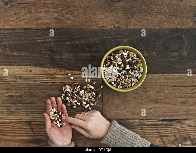 A person sorting different kinds of beans and pulses in her hands on a wooden table top - Stock Image