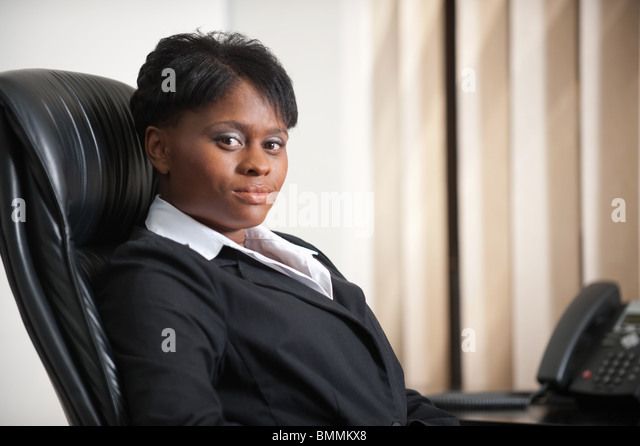 Portrait of businesswoman at desk, Johannesburg, Gauteng Province, South Africa - Stock Image