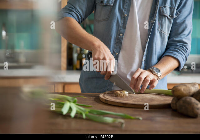 Man cutting spring onion - Stock Image