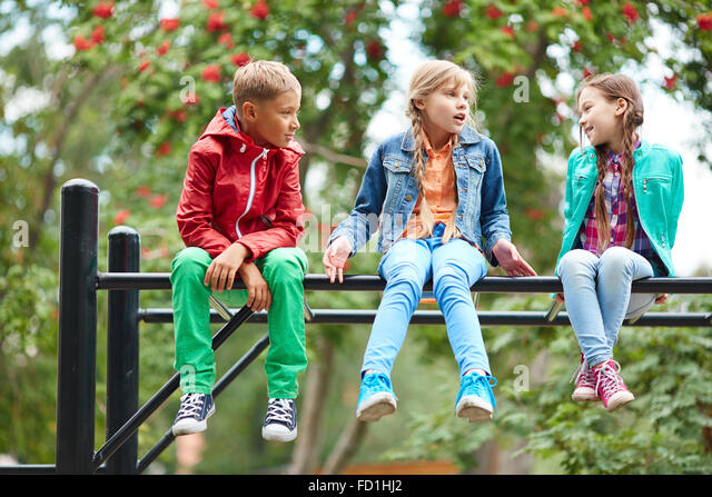 Happy kids talking while sitting on recreational facilities - Stock Image