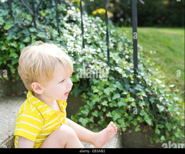 Boy sitting on steps - Stock Image